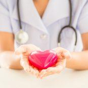 Female nurse with stethoscope holding heart